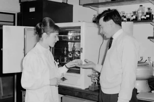 Old black and white photo of man and woman in lab.